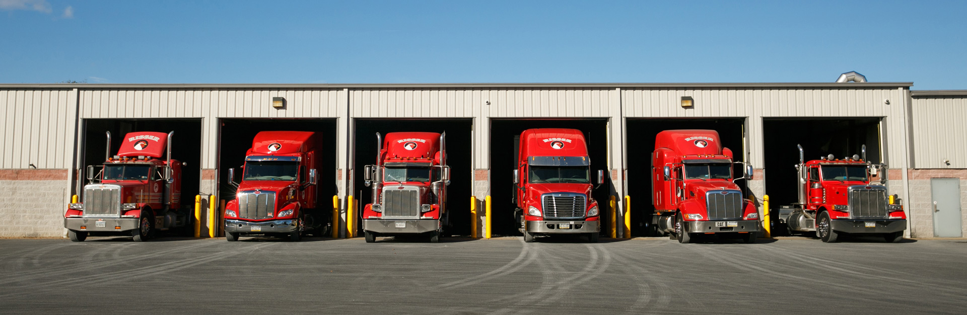Various size trucks lined up outside of garage bay