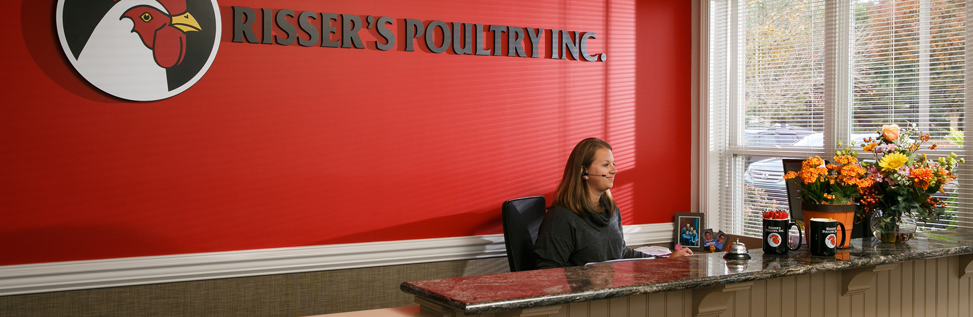 Receptionist working at the front desk of the Risser's Poultry office